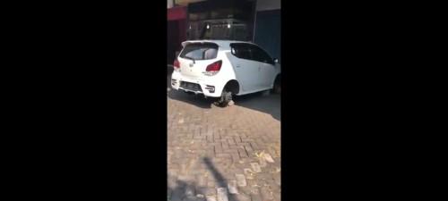 Mobil Ayla yang terparkir dengan velg dan ban yang telah dicuri. (Ist)