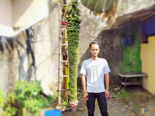 Titor bersama pohon pisang di samping rumahnya yang berbuah tak seperti umumnya pisang. (Anggara Sudiongko/MalangTIMES)
