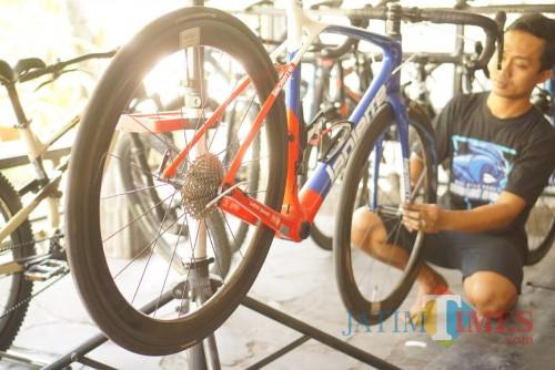 Angga saat menyervis sepeda di bengkelnya (Joko Pramono for Jatim TIMES)