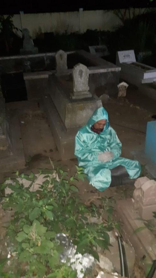 Petugas makam yang nampak beristirahat di samping batu nisan menunggu jenazah datang(Ist)