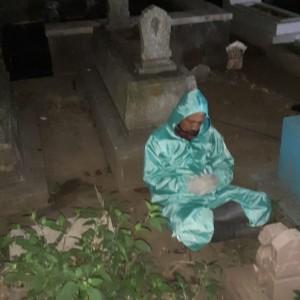 Mengharukan, Petugas Pemakaman yang Kelelahan Tertidur di Samping Batu Nisan