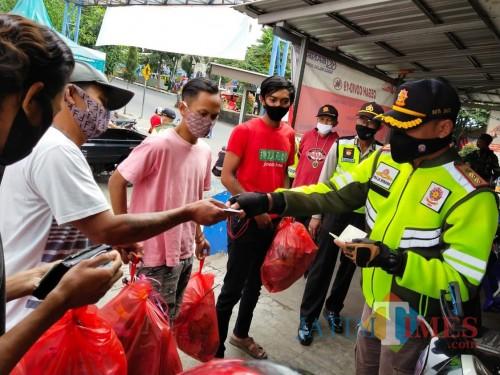 Beberapa pemuda saat akan mengumpulkan sampah kepada petugas saat patroli di Pasar Besar Kota Batu, Minggu (5/7/2020). (Foto: istimewa)