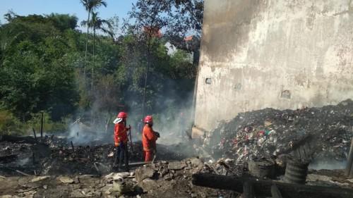 Lokasi gudang barang bekas yang terbakar, nampak petugas terus berupaya memadamkan api (Ist)