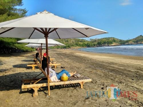 Wisatawan tampak bersantai di Pantai Serang, Blitar.(Foto : Malik Naharul/BlitarTIMES)