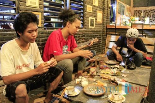 Beberapa anak muda sambil ngopi dan meracik rokok tingwe di Kedai Tengwe (Eko Arif S/ JatimTIMES)