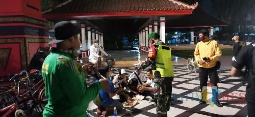 Petugas menertibkan warga yang berkerumun di tempat publik di Kota Blitar.