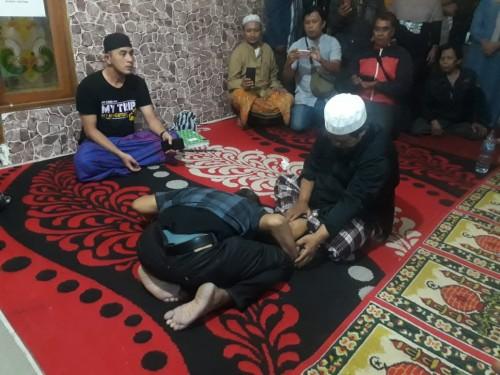 Gus Idris dengan Kyai Rodyallah sedang menangani pasien dari daerah Tuban yang datang ke Ponpes Thoriqul Jannah, Ngajum, Kabupaten Malang, Sabtu (11/7/2020) dini hari. (Foto: Tubagus Achmad/MalangTimes)