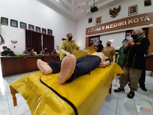 Petugas memberikan tata cara pemulasaraan jenazah covid 18.(eko arif s/Jatimtimes)