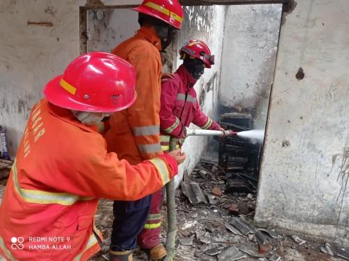 Petugas Damkar saat melakukan pembasahan areal rumah kosong yang terbakar (Ist)
