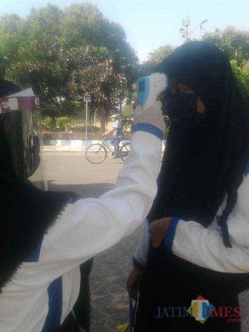 Sebelum masuk lingkungan sekolah, siswa diperiksa suhu tubuh