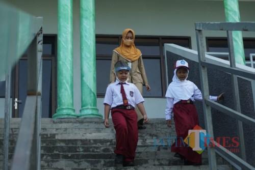 Sejumlah siswa baru SDN Kepanjen 2 Jombang terlihat didampingi guru saat berkeliling lingkungan sekolah. (Foto : Adi Rosul / JombangTIMES)