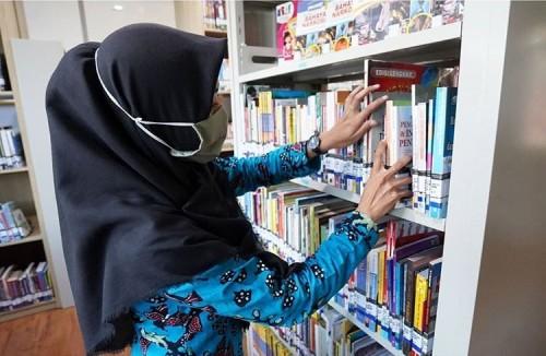 Salah satu petugas saat mengecek koleksi buku di perpustakaan Balai Kota Among Tani.