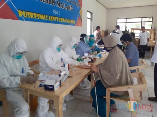 Petugas kesehatan dari Puskesmas Janti saat melakukan rapid test terhadap warga RSBN Malang, Rabu (15/7). (Arifina Cahyanti Firdausi/MalangTIMES).