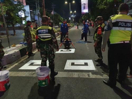 Petugas gabungan yang tengah melakukan pembuatan marka physical distancing (Ist)