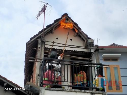 Petugas Damkar saat mengevakuasi sarang tawon vespa di rumah warga (Joko Pramono for Jatim TIMES)