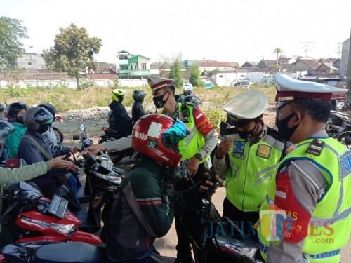 Petugas kepolisian saat memeriksa kendaraan di kawasan Jalan Ahmad Yani (Anggara Sudiongko/ MalangTIMES)