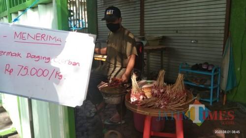 M. Anshor saat membakar sate pesanan pelanggan yang memanfaatkan jasa permak dagingnya. (Joko Pramono for Jatim TIMES)