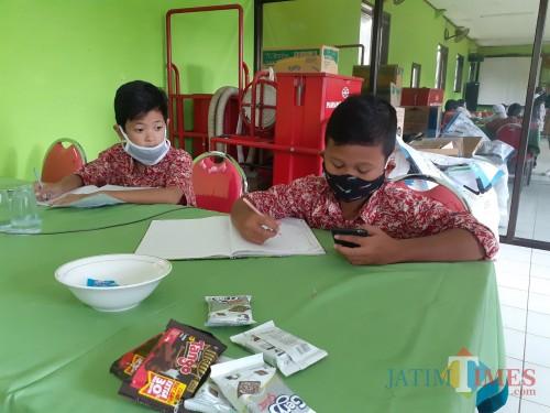 Para siswa SD saat menjalani sekolah daring dengan memanfaatkan wifi gratis di Kelurahan Bandulan, Kecamatan Sukun, Kota Malang, Selasa (4/8). (Arifina Cahyanti Firdausi/MalangTIMES).