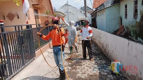 Relawan PMI Kabupaten Jember saat melakukan penyemprotan disinfektan di rumah-rumah warga (foto: Puji SN / JatimTIMES)