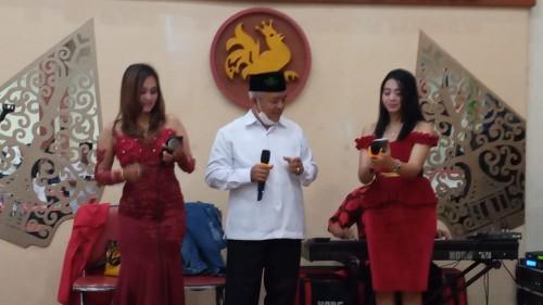 Sanusi saat bernyanyi diatas panggung dengan didampingi dua penyanyi dangdut (Ist)