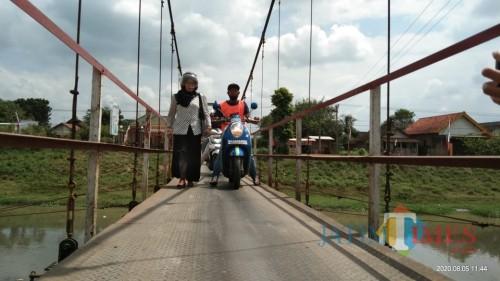 Salah satu warga yang takut melintas di jembatan gantung dibantu oleh penjaga jembatan (Joko Pramono for Jatim TIMES)