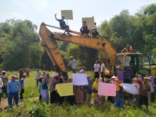 Warga membentangkan poster tuntutan di alat berat yang berada di lokasi calon tambang galian C. (Istimewa)