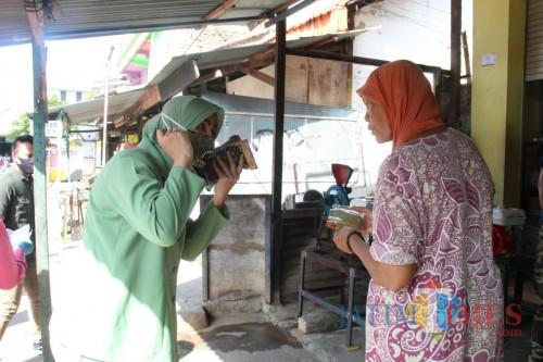 Ketua Bhayangkari cabang Sumenep Risma Saripati saat memberikan masker gratis pada pengunjung pasar (Foto: Ist/JatimTIMES)