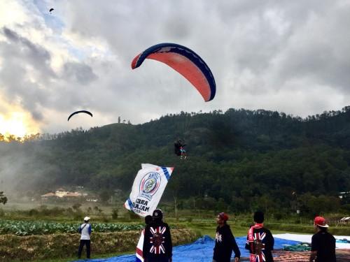 Bendera Arema saat diterbangkan oleh penerbang paralayang di Lapangan Songgomaruto, Kelurahan Songgokerto, Kecamatan Batu,Selasa (11/8/2020). (Foto: Irsya Richa/MalangTIMES)