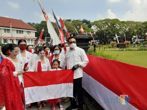 Wakil Wali Kota Malang Sofyan Edi Jarwoko (paling kanan) saat serah terima pembentangan bendera merah putih sepanjang 366 meter di Alun-Alun Tugu Kota Malang, Minggu (16/8). (Arifina Cahyanti Firdausi/MalangTIMES).