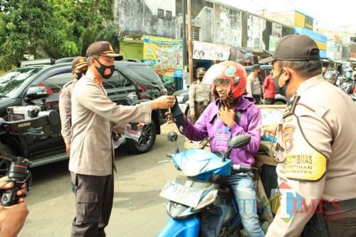 Kapolres Jember AKBP. Aris Supriyono saat membagikan masker kepada pengendara di sekitar pasar Tanjung Jember (foto : istimewa / Jatim TIMES)