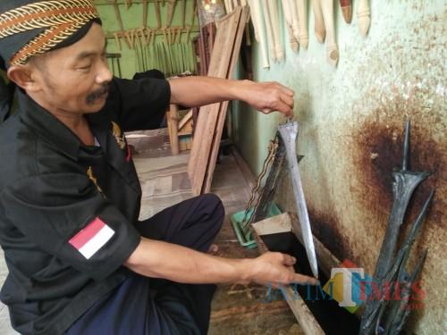 Sudahri (51), saat mencuci keris pelanggannya. (Foto : Adi Rosul / JombangTIMES)