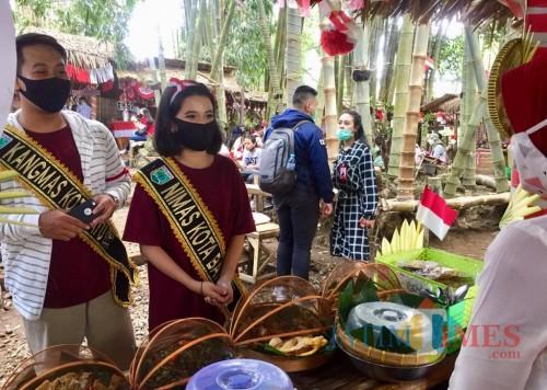 Kangmas Nimas saat membeli hasil olahan warga di Pasar Bring Harjo, Desa Junrejo, Kecamatan Junrejo. (Foto: Irsya Richa/MalangTIMES)