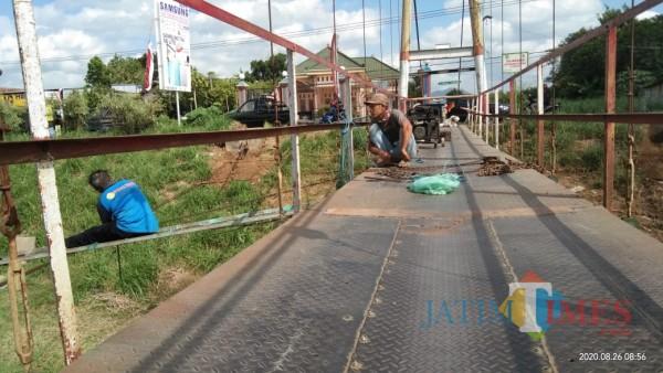 Proses perbaikan dan penggantian seling jembatan gantung yang putus. (Joko Pramono for Jatim TIMES)