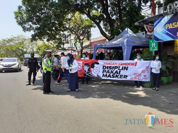 Petugas dari Polkesma saat membagikan masker kepada pedagang di Pasar Oro-Oro Dowo Kota Malang, Kamis (27/8). (Arifina Cahyanti Firdausi/MalangTIMES).