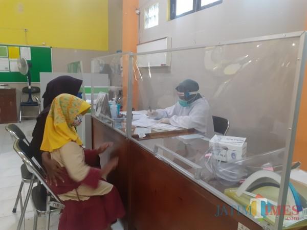 Pelayanan pasien di Puskesmas Kedungkandang dengan protokol Covid-19. (Arifina Cahyanti Firdausi/MalangTIMES).