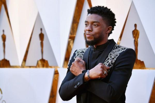 """Aktor Black Panther, Chadwick Boseman menunjukkan simbol """"Wakanda Forever"""" dengan menyilangkan lengannya (foto: Jeff Kravitz/Getty Images)"""