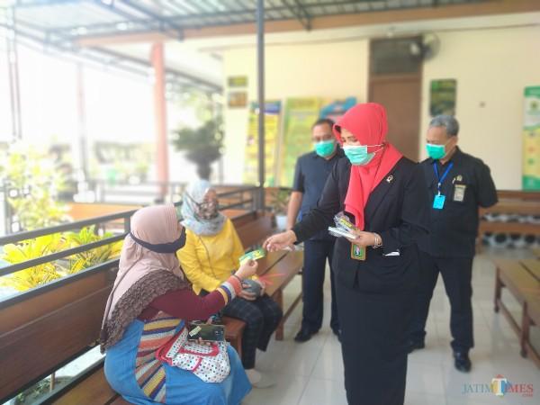 Ketua PN Kota Malang, Nuruli Mahdilis saat memberikan stiker ajakan untuk tidak memberikan gratifikasi pada pegawai pengadilan (Anggara Sudiongko/MalangTIMES)