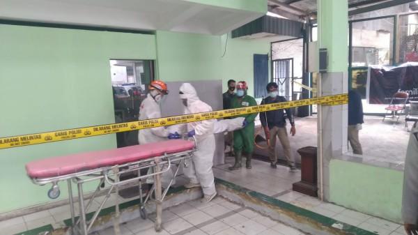Petugas saat tengah melakukan evakuasi jasad korban dari dalam kamar bengkel (Ist)
