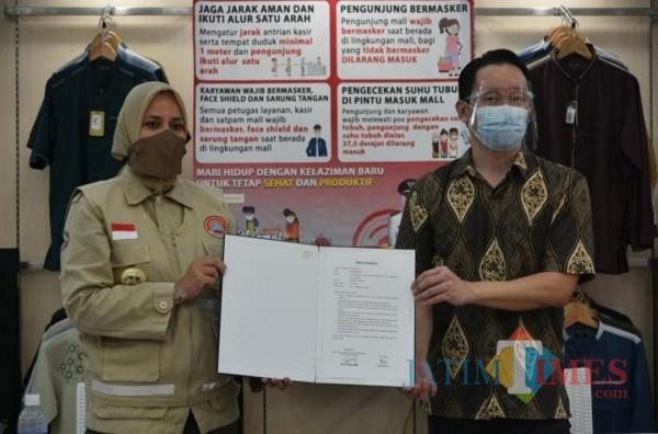 Bupati Faida menyerahkan sertifikat Toko Tangguh kepada Adi Susanto