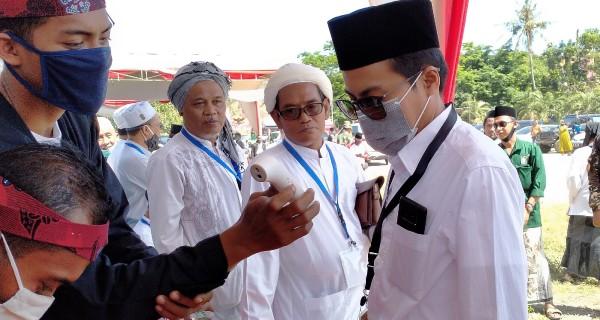 KH. Salahuddin Warist atau Ra Mamak mengikuti serangkaian protokol kesehatan covid-19 di KPU Sumenep (Foto: Syaiful Ramadhani/JatimTIMES)