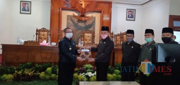 Bupati Tulungagung Maryoto Birowo (kiri, masker putih) menerima penetapan Perubahan APBD dari Marsono.  (foto : Joko Pramono/Jatim Times)