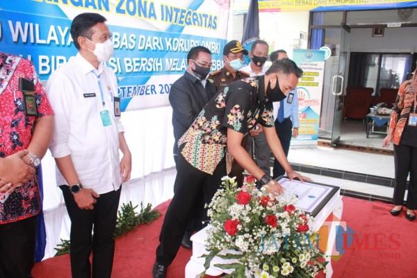 Kepala BNN Kabupaten Malang, Letkol Laut (PM) Candra Hermawan (merunduk) beserta jajaran Forkopimda saat hendak menandatangani plakat zona integritas