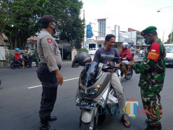 Anggota Polsek dan Koramil Kota Lumajang bagi masker kepada warga (Foto : Moch. R. Abdul Fatah / Jatim TIMES)