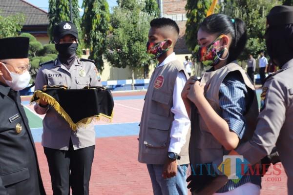 Bupati Sumenep A. Busyro Karim saat memakaikan masker dan rompi pada duta anti narkoba di Mapolres Sumenep (Foto: Humas Polres Sumenep for JatimTIMES)