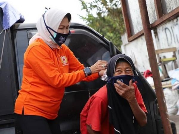 Wali Kota Batu Dewanti Rumpoko saat memasangkan masker kepada lansia di pinggi jalan Kota Batu. (Foto: instagram Dewanti_Rumpoko)