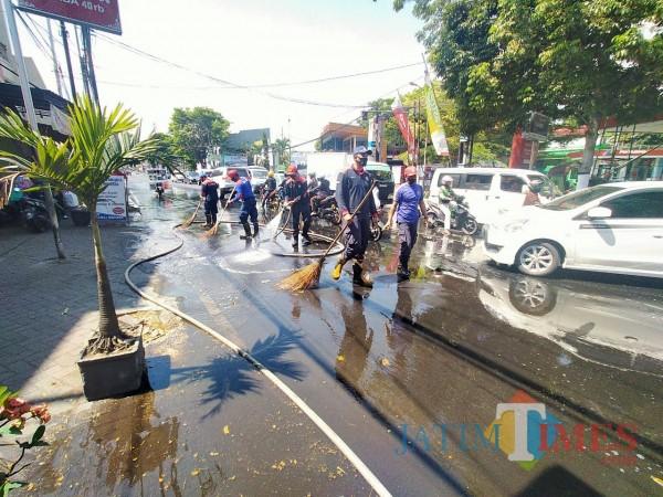 Petugas PMK Kita Malang yang tengah berupaya membersihkan jalan dari cecerna solar (Anggara Sudiongko/MalangTIMES)