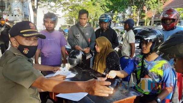 Petugas saat melakukan pendataan kepada sejumlah warga yang melanggar protokol kesehatan dengan tidak memakai masker