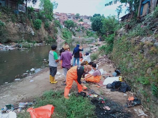 Suasana petugas kebersihan DLH Kota Malang bersama komunitas sedang memungut sampah di sungai (DLH for MalangTIMES)