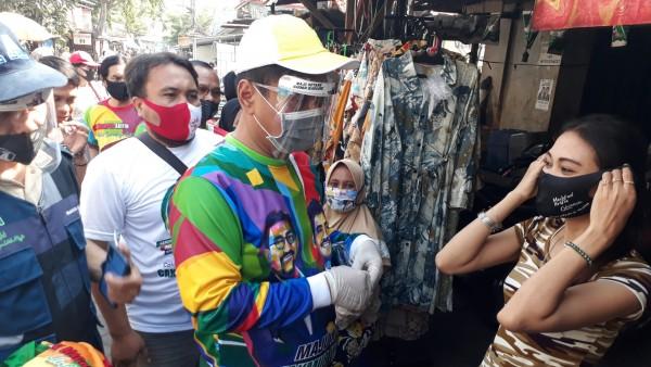 Mujiaman Sukirno saat membagikan masker ke warga