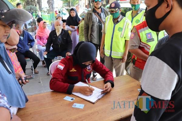Petugas gabungan saat mengecek identitas warga yang melanggar protokol kesehatan dengan tidak memakai masker (Foto: Ist/JatimTIMES)